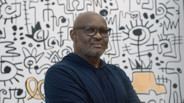 """Victor Ekpuk with his installation """"Harlem Sunrise"""" at The Africa Center."""